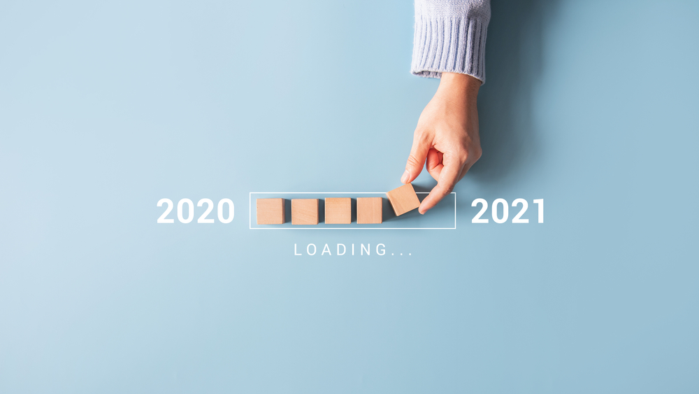 Shutterstock_1831823293 Loading new year 2020 to 2021 with hand putting wood cube in progress bar.