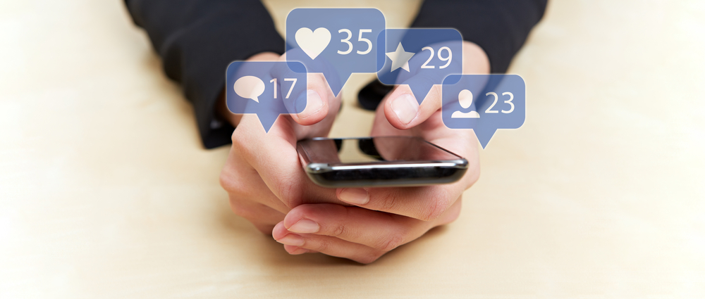 Shutterstock_730530235 Hands holding smartphone with social media or social network notification icons