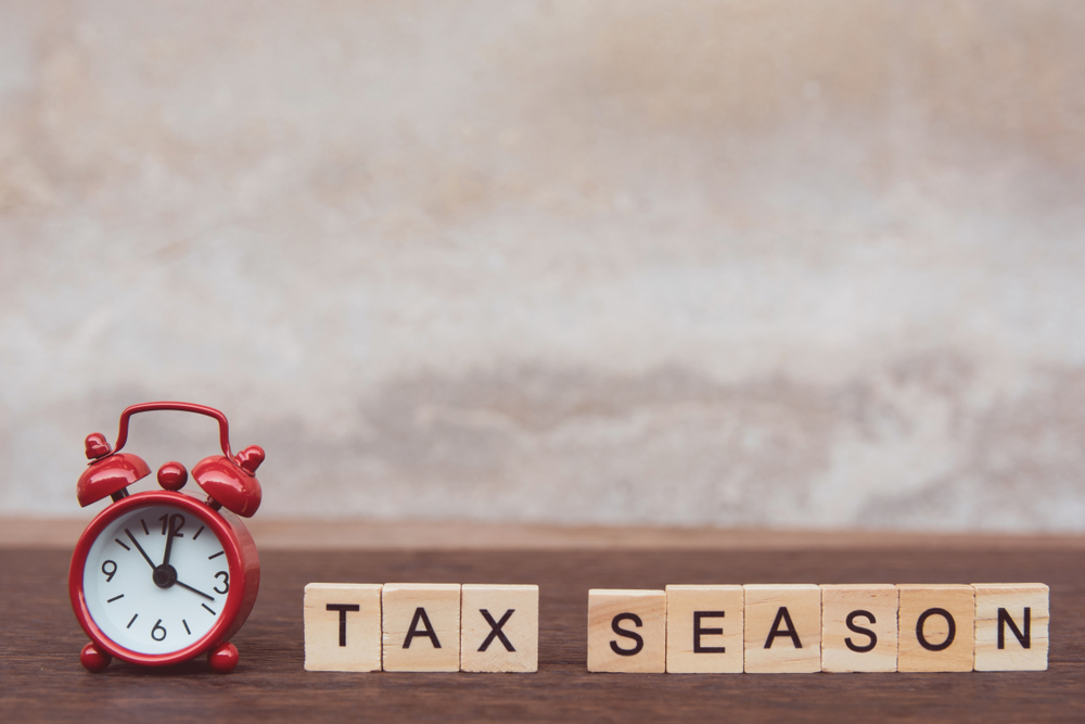 Shutterstock_1307067850 Tax season with wooden alphabet blocks and Red alarm clock, on Table dark plank wooden background with copy space
