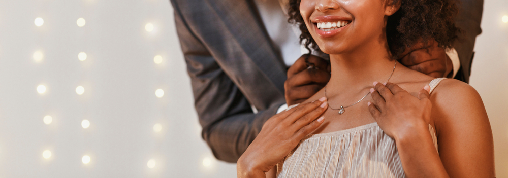 Shutterstock_1628382697 Gift for Valentine's Day. Cropped of african man putting beautiful necklace on woman neck, panorama with free space