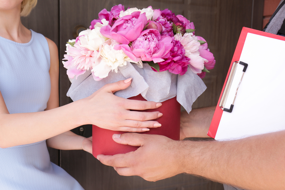 Shutterstock_681763810 Young woman receiving beautiful peony flowers from delivery man