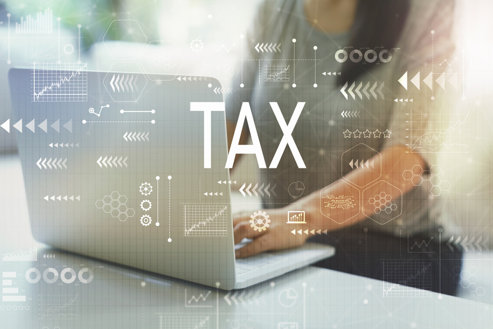 Shutterstock_1229040460 Tax with woman using her laptop in her home office