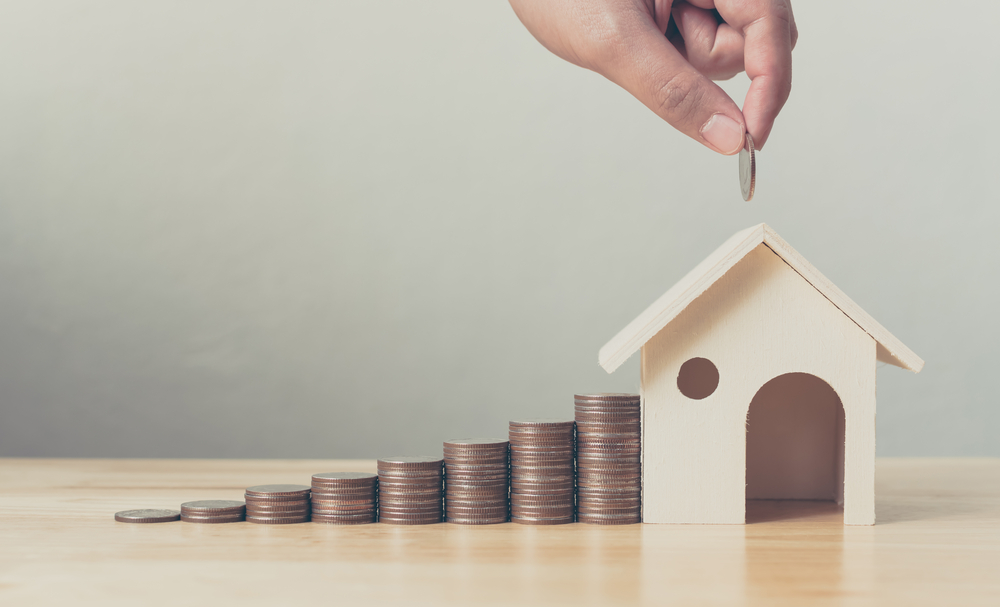 Shutterstock_757649455 Property investment and house mortgage financial concept, Hand putting money coin stack with wooden house