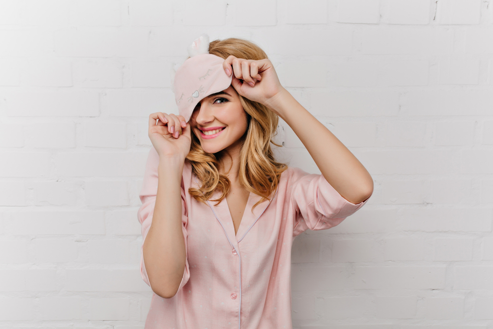 Shutterstock_1068890639 Pale smiling girl with curly hair playfully posing on white background. Chilling woman in eyemask and silk pajama laughing at home.