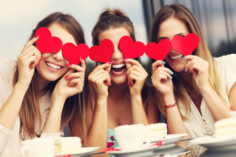 Shutterstock_450244624 Picture presenting three girlfriends holding hearts in cafe