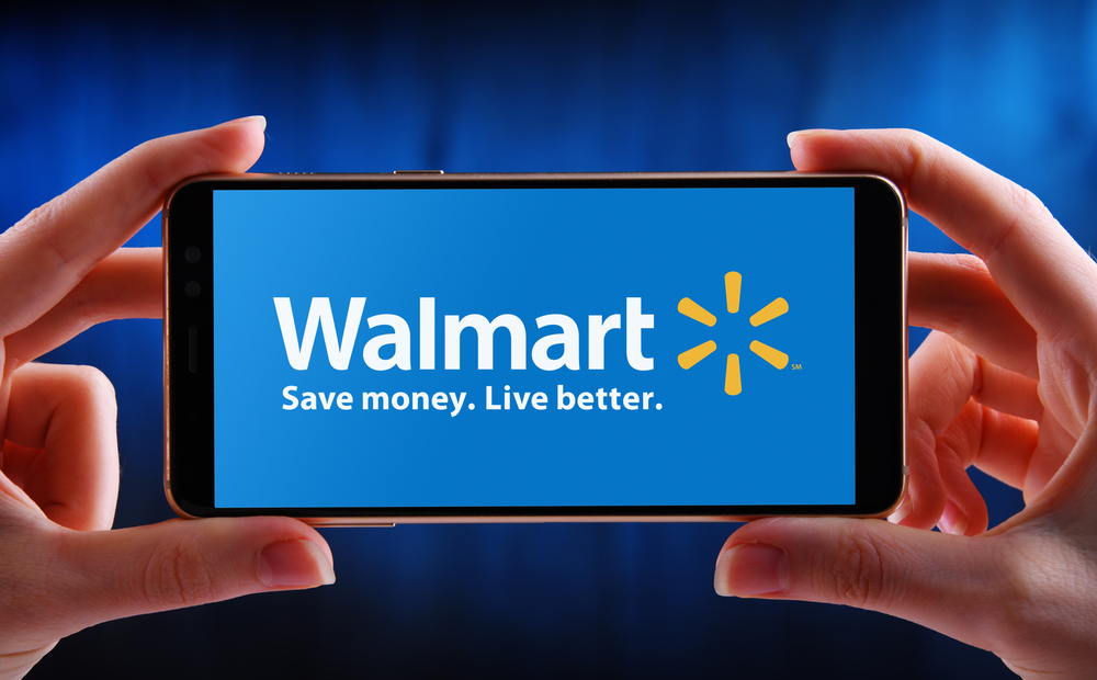 Shutterstock_1782067727 POZNAN, POL - MAY 21, 2020: Hands holding smartphone displaying logo of Walmart Inc., an American multinational retail corporation headquartered in Bentonville, Arkansas