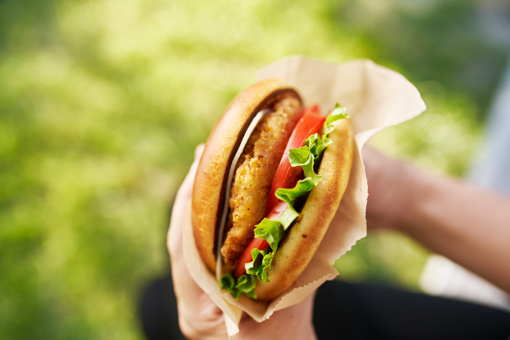 Shutterstock_1155619603 woman holding crispy chicken sandwich from first person view