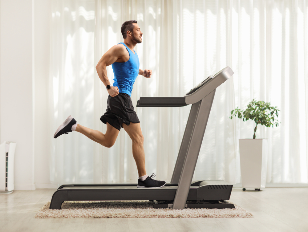 Shutterstock_1495412588 Full length profile shot of a young man running on a treadmill at home