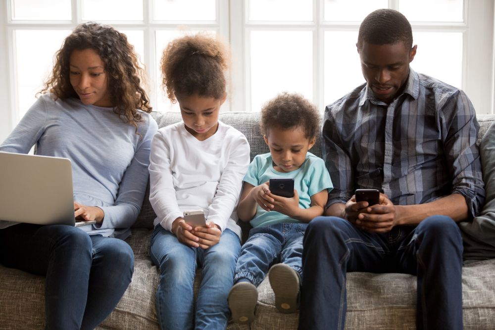 Shutterstock_1282523578 African american family with kids using laptop and mobile phones at home, black parents and little children addicted to devices, gadgets dependence overuse, internet social media addiction concept