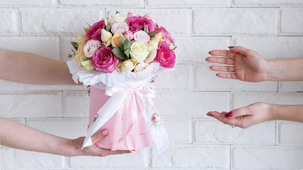 Shutterstock_648381583 Delivery of a floral workshop. The customer receives his order-a bouquet of pink and pale yellow roses. Hand courier pass flowers to the buyer
