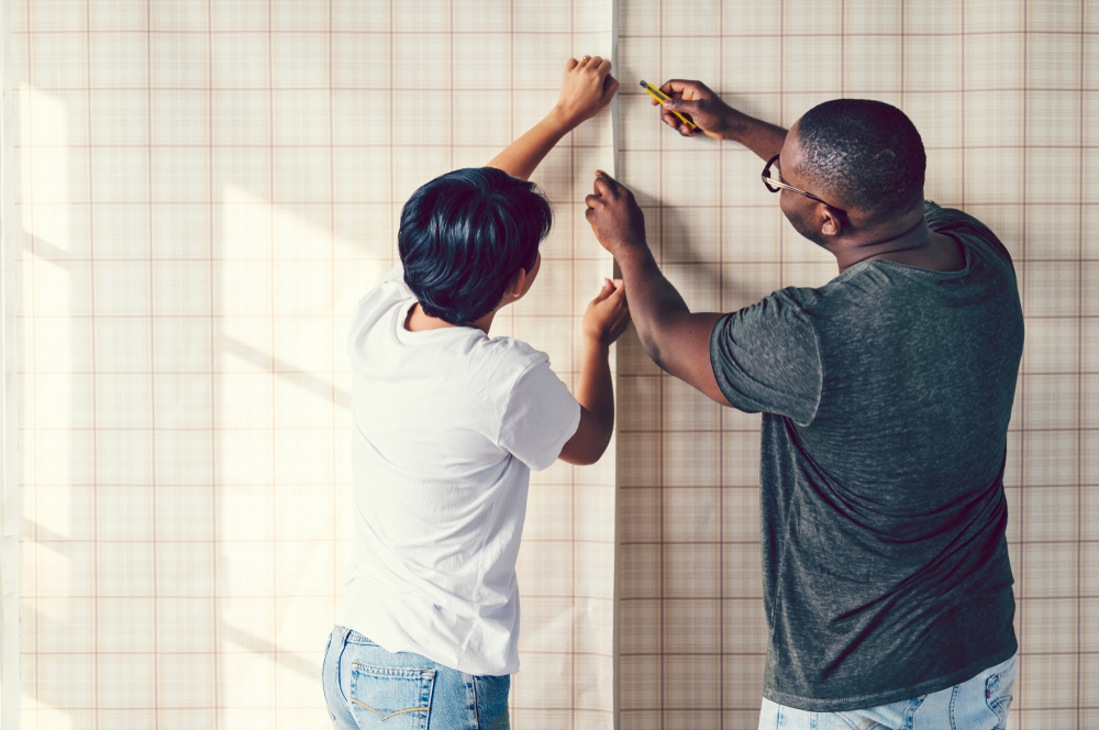 Shutterstock_1101030047 Couple decorating putting up a wallpaper