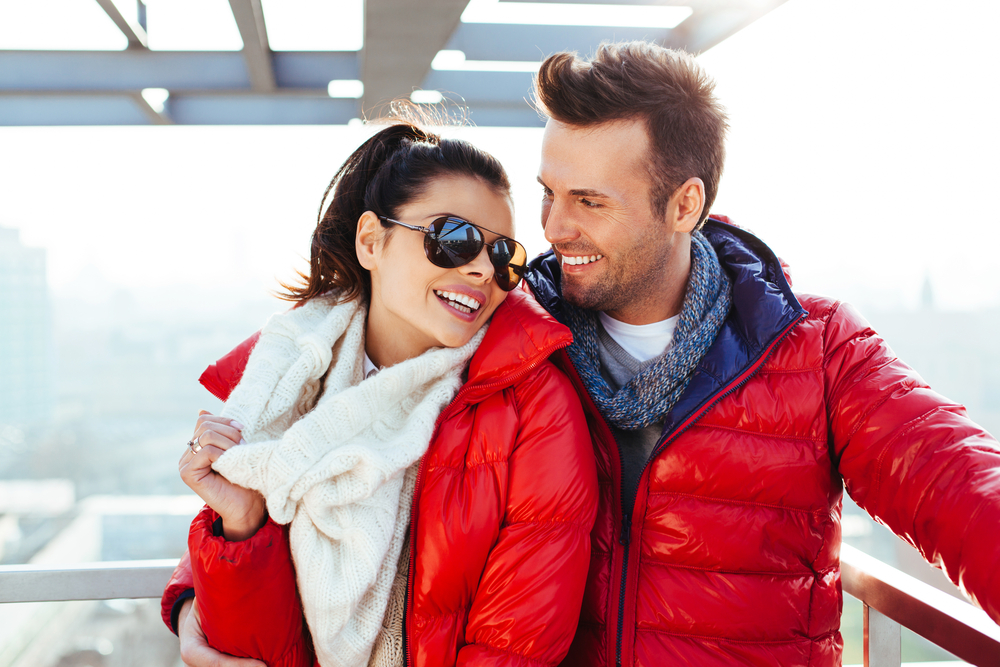 Shutterstock_226628890 Young couple together at rooftop smiling