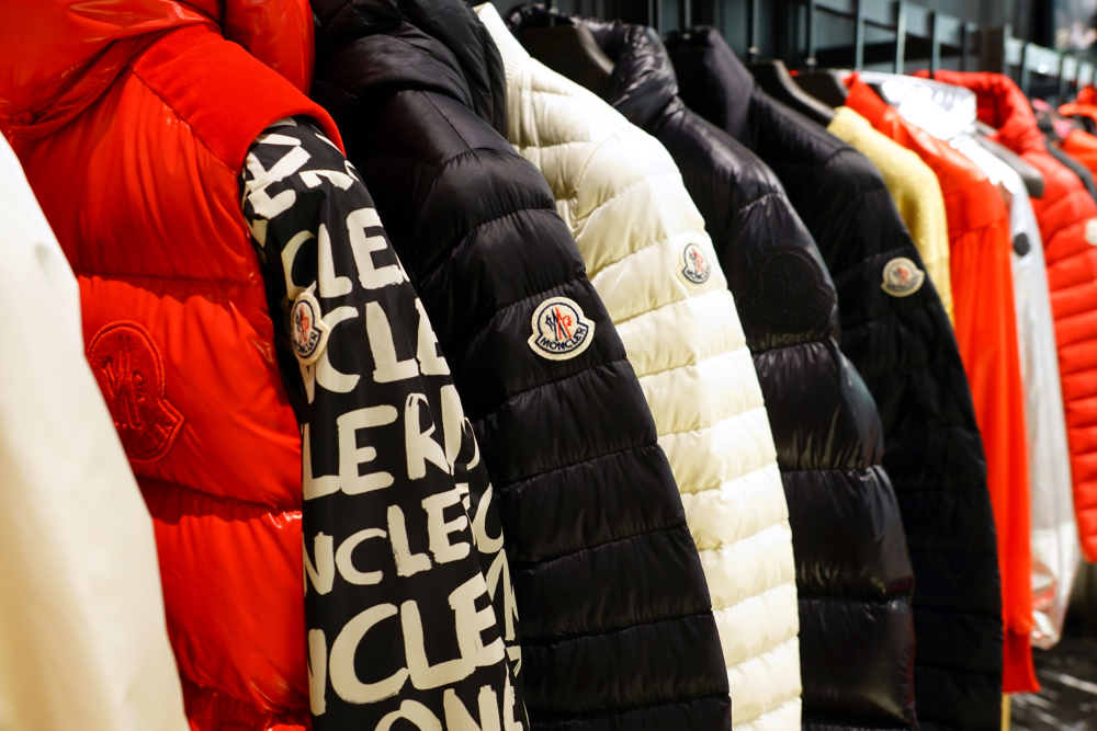Shutterstock_1419326627 VENICE, ITALY -10 APR 2019- View of winter clothes in a Moncler store. Monclerc is a fashion brand known for its fashionable down jackets.