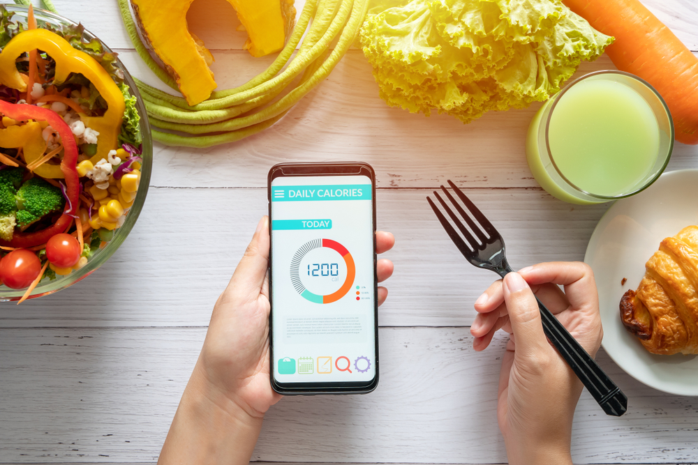 Shutterstock_1465238459 Calories counting , diet , food control and weight loss concept. woman using Calorie counter application on her smartphone at dining table with salad, fruit juice, bread and vegetable