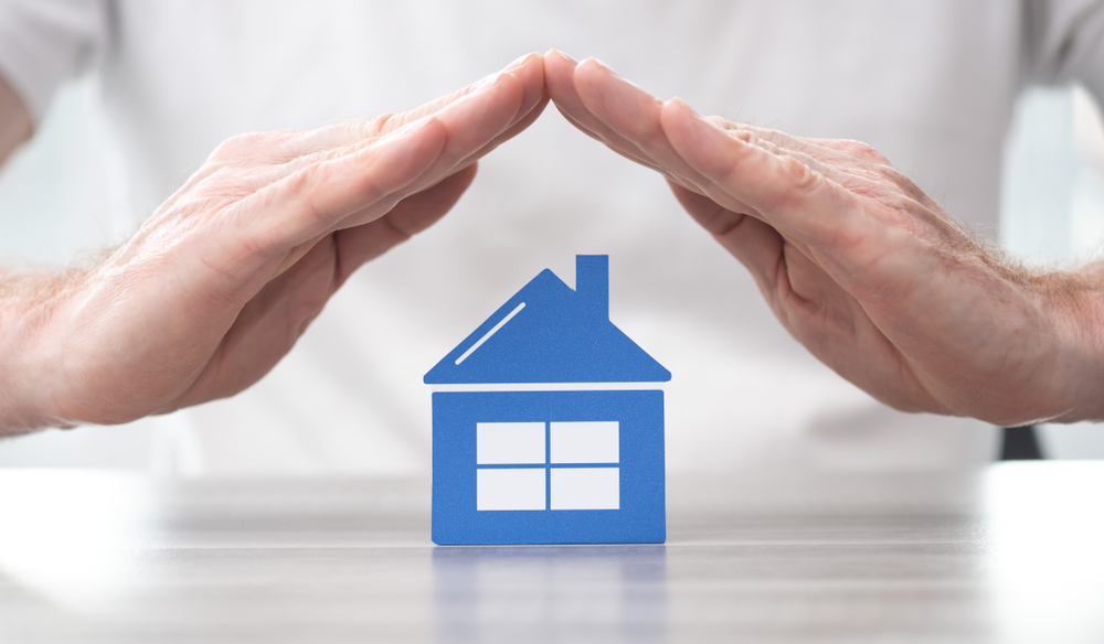 Shutterstock_1507496672 House protected by hands - Concept of home insurance