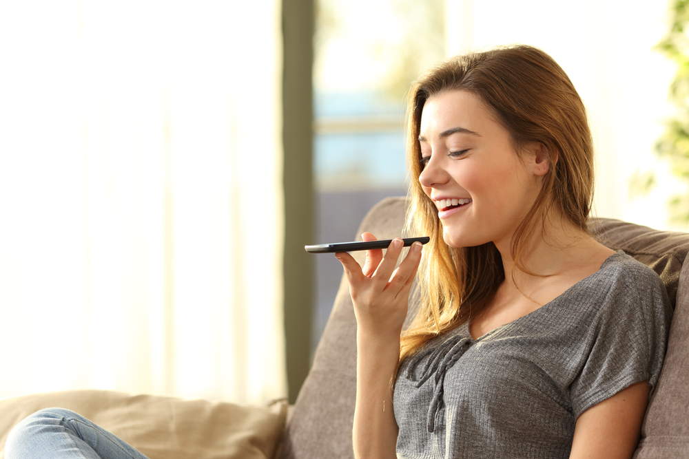 Shutterstock_552056272 Girl using a smart phone voice recognition on line sitting on a sofa in the living room at home with a warm light and a window in the background