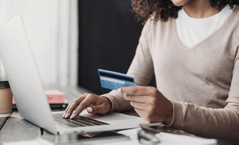 Shutterstock_1840890145 Online shopping. Young woman holding credit card and using laptop at home. Payment online, e-commerce, internet banking, spending money, ordering delivery, business, finance concept