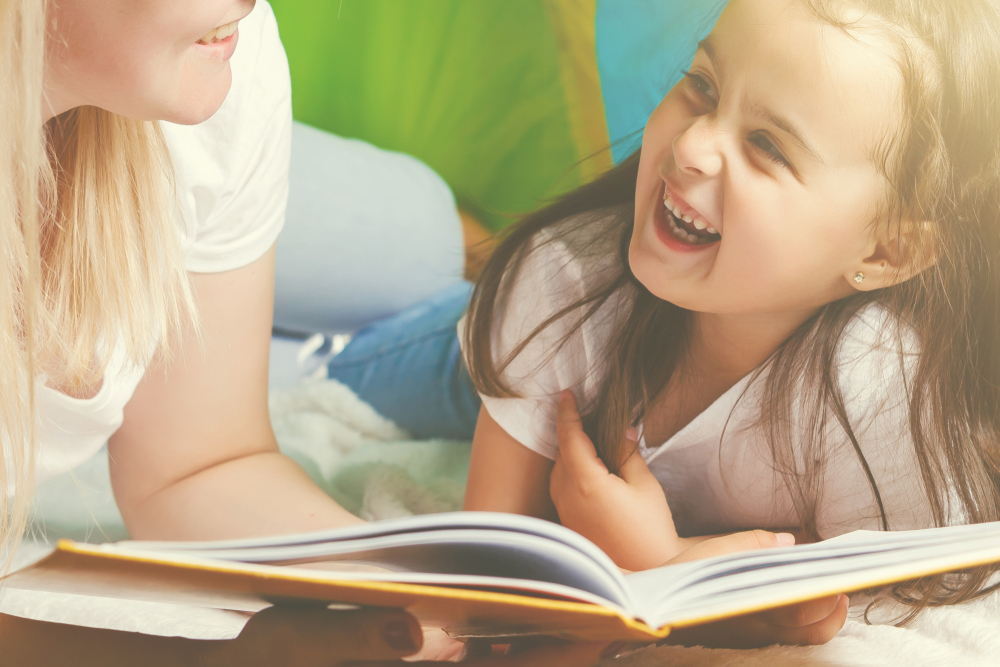 Shutterstock_1009685893 Happy loving family. Pretty young mother reading a book to her daughter tent, indoors