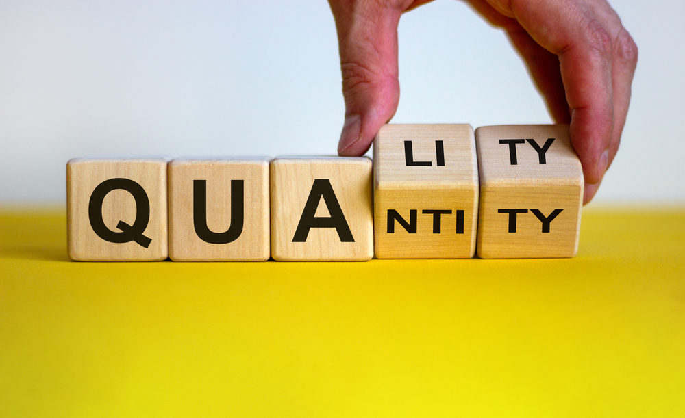 Shutterstock_1816118867 Quality over quantity. Hand turns cubes and changes the word 'quantity' to 'quality'. Beautiful yellow table, white background, copy space. Business concept.