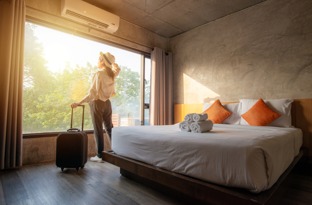 Shutterstock_1494850982 Portrait of tourist woman standing nearly window, looking to beautiful view with her luggage in hotel bedroom after check-in. Conceptual of travel and vacation.