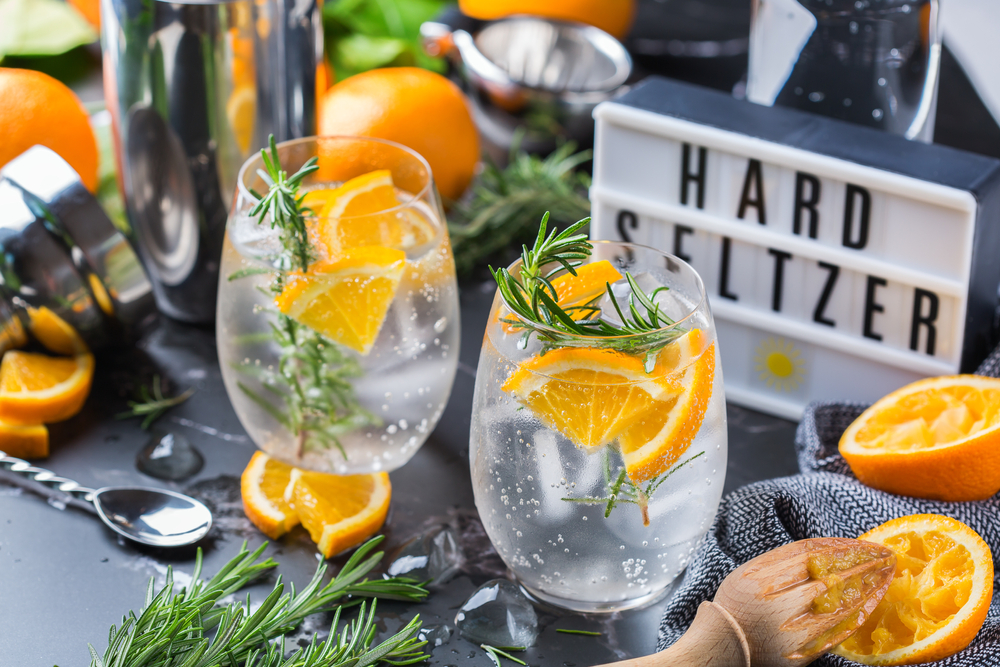 Shutterstock_1933047041 Hard seltzer cocktail with orange, rosemary and bartenders accessories