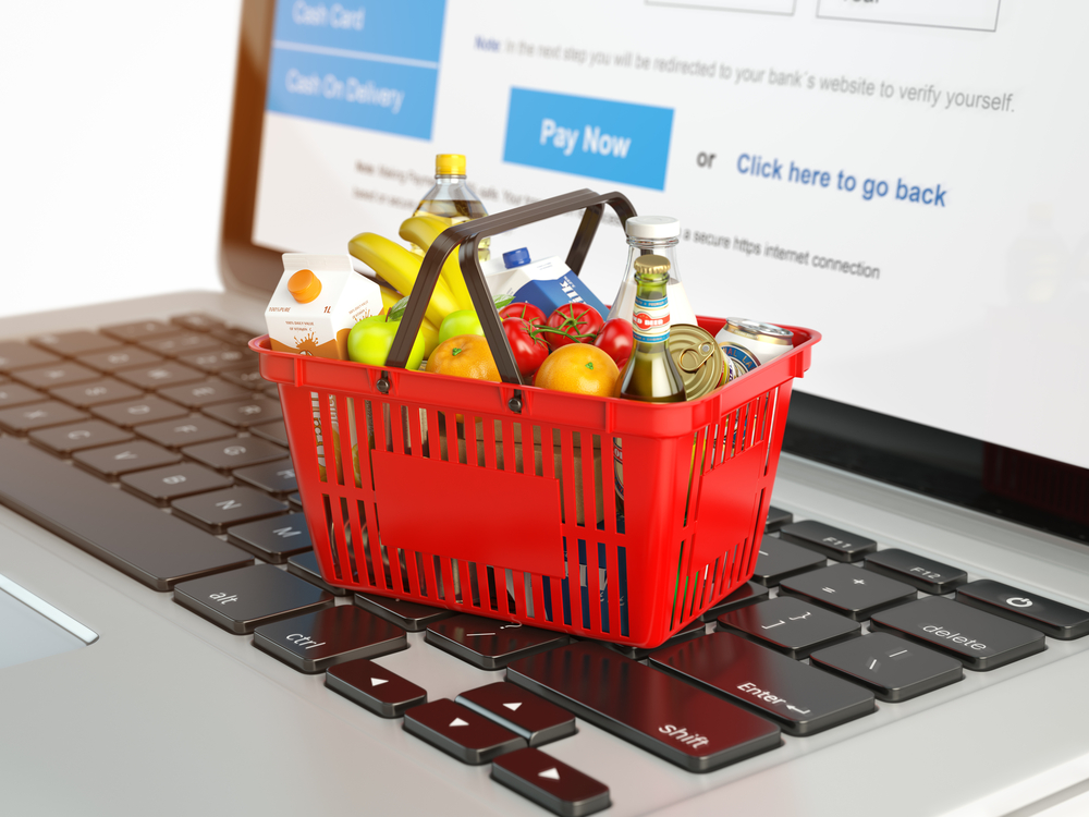 Shutterstock_581283208 Shopping basket with variety of grocery products ion laptop keyboard. E-commerce concept 3d illustration