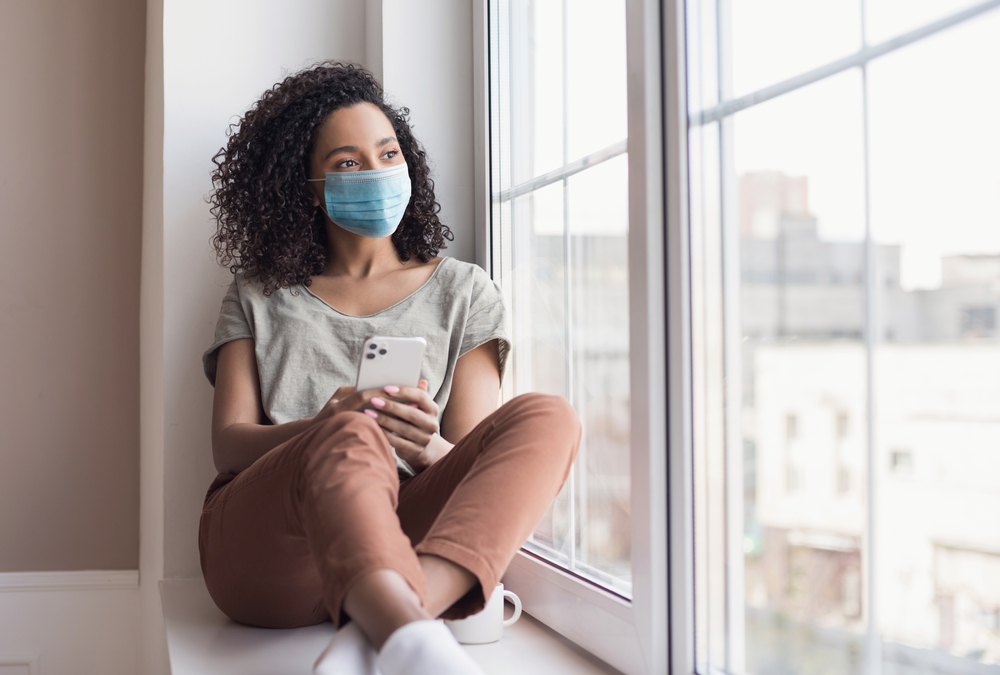 Shutterstock_1864147915 Sad woman alone during coronavirus pandemic wearing face mask indoors at home for social distancing. Mixed race girl looking at window. Anxiety, stress, lockdown, mental health crisis concept