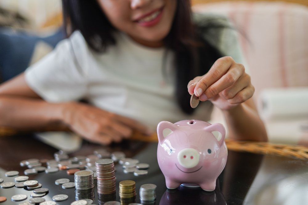 Shutterstock_1689229639 Woman is smiling and hand putting coin into piggy bank, Finance or Savings concept.