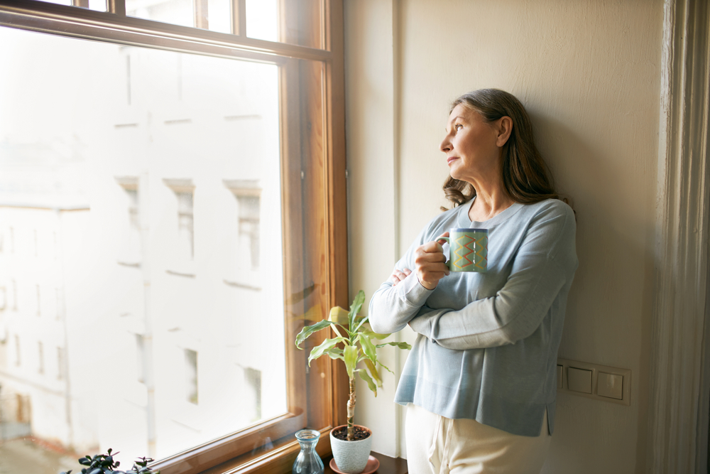 Shutterstock_1756606511 Portrait of thoughtful retired mature woman in casual clothes standing by large window, leaning on white wall, looking outside, drinking tea. People, social distancing and quarantine concept