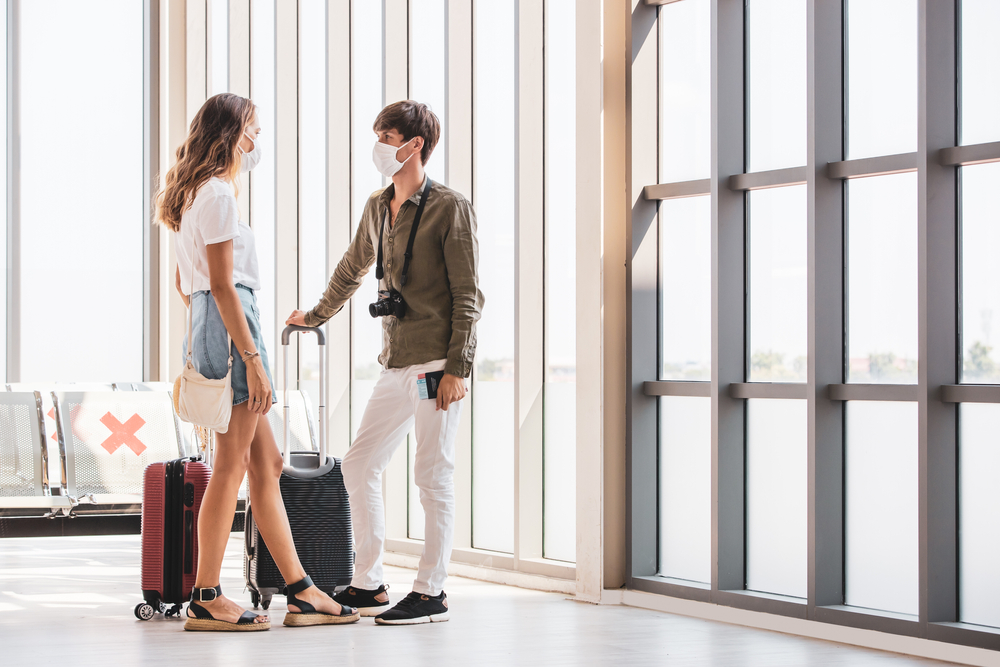 Shutterstock_1807136362 Two Caucasian tourists wearing protective hygiene mask holding passport standing beside luggage and talking at airport while waiting for flight. Concept for new normal travel in coronavirus outbreak.