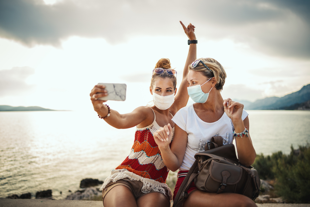 Shutterstock_1797696529 Shot of attractive female friends wearing with protective mask and making selfie with smartphone while exploring the wonderful city of Mediterranean.