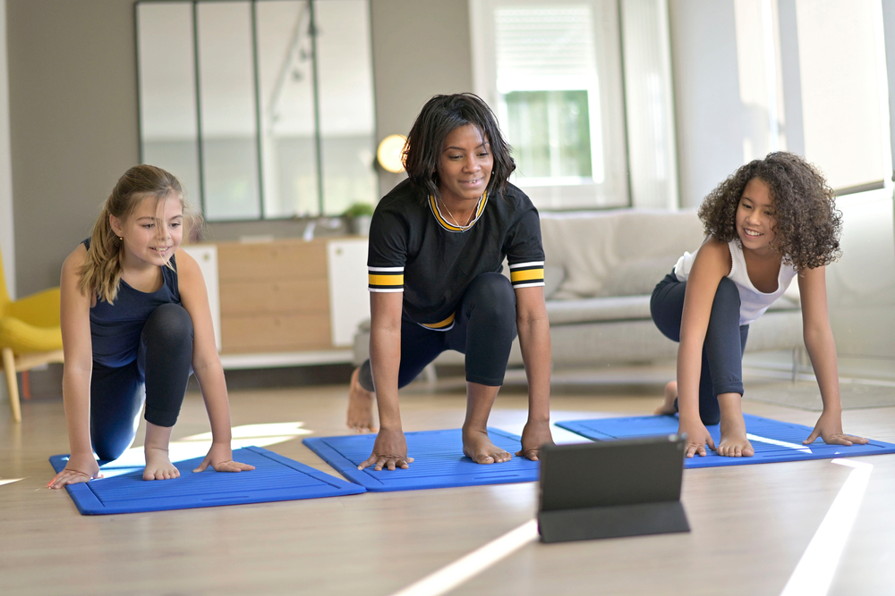 Shutterstock_1864409731 Young woman with kids doing fitness exercices at home, online class