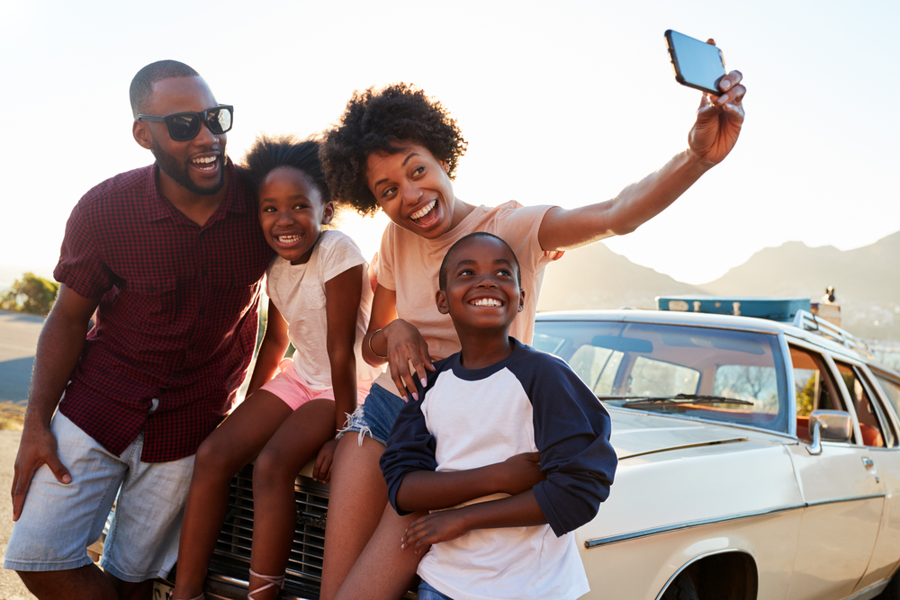 Shutterstock_670636564 Family Posing For Selfie Next To Car Packed For Road Trip