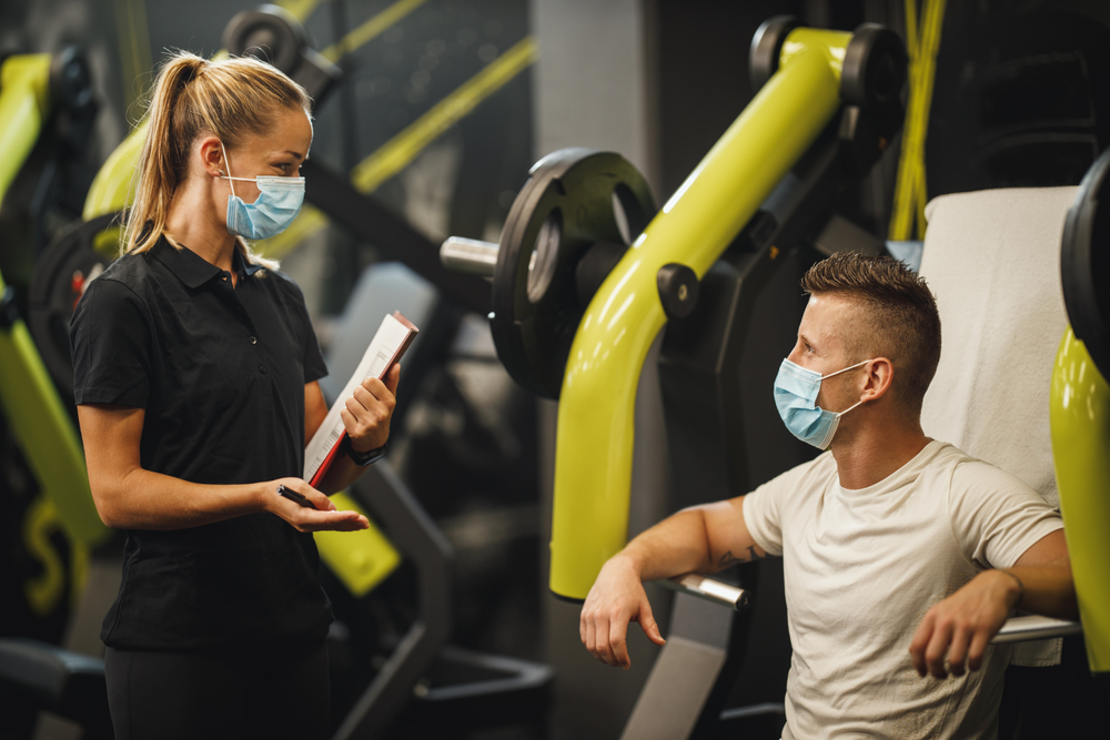 Shutterstock_1810621222 Shot of a muscular young woman with protective mask working out with personal trainer at the gym machine during Covid-19 pandemic. She is pumping up her chest muscule with heavy weight.