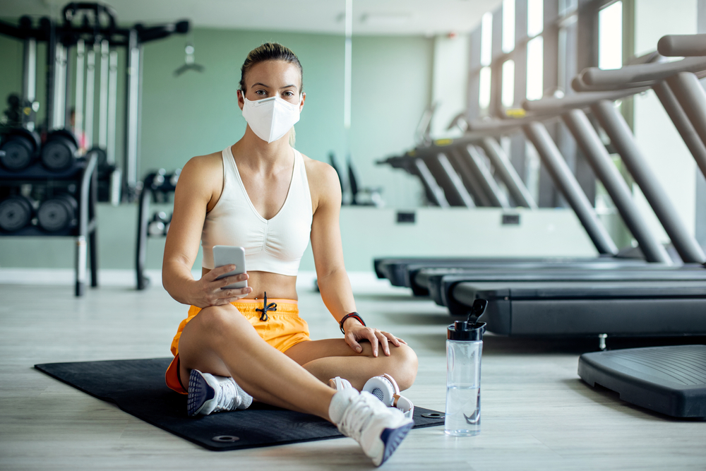 Shutterstock_1780968569 Athletic woman with face mask using smart phone while relaxing on the floor after working out in a gym during coronavirus epidemic.