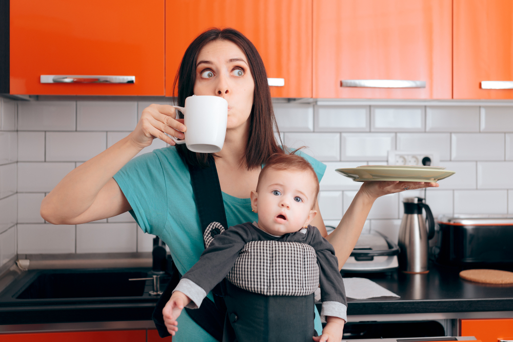 Shutterstock_1620417934 Busy Multitasking Mom with Baby, Coffee Mug and Dishes. Tired mother needing caffeine to do the household chores