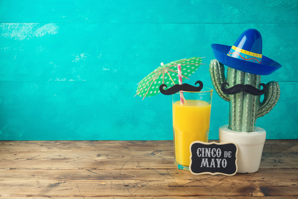 Shutterstock_1368173774 Cinco de Mayo holiday background with Mexican cactus, party sombrero hat and orange juice on wooden table