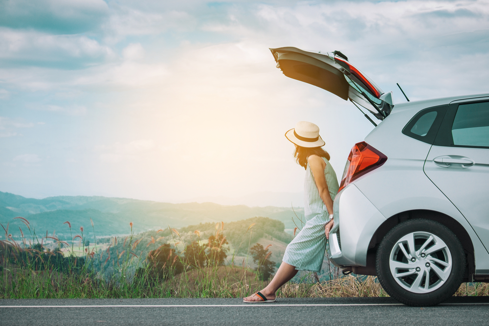 Shutterstock_517237099 Woman traveler sitting on hatchback car with mountain background in vintage tone