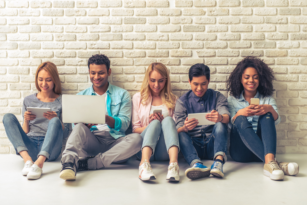 Shutterstock_428460970 Beautiful young people of different nationalities are using gadgets and smiling, sitting against white brick wall