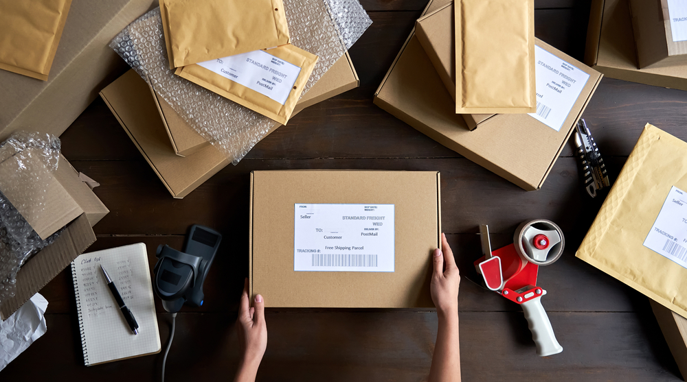 Shutterstock_1831476562 Above table top view of female warehouse worker or seller packing ecommerce shipping order box for dispatching, preparing post courier delivery package, dropshipping shipment service concept.