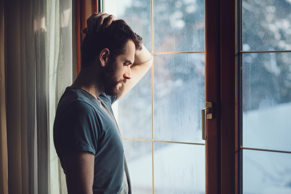Shutterstock_558962893 Young sad mad sitting by the window in regret