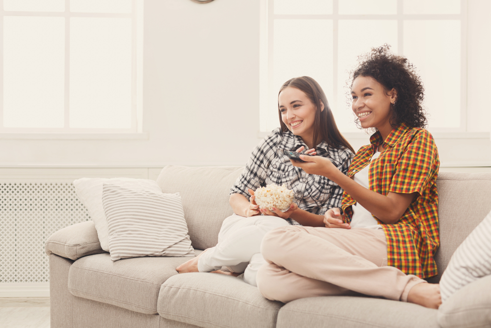 Shutterstock_790678639 Smiling young women relaxing and watching TV at home, female friends having rest after hard week, copy space