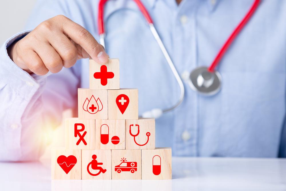 Shutterstock_1937633761 Medical health care wood block icon technology orage light len flare effect, concept hand health care protection medical icon, heart, ambulance, stethoscope, medicine, blood, Red Cross, wheelchair.