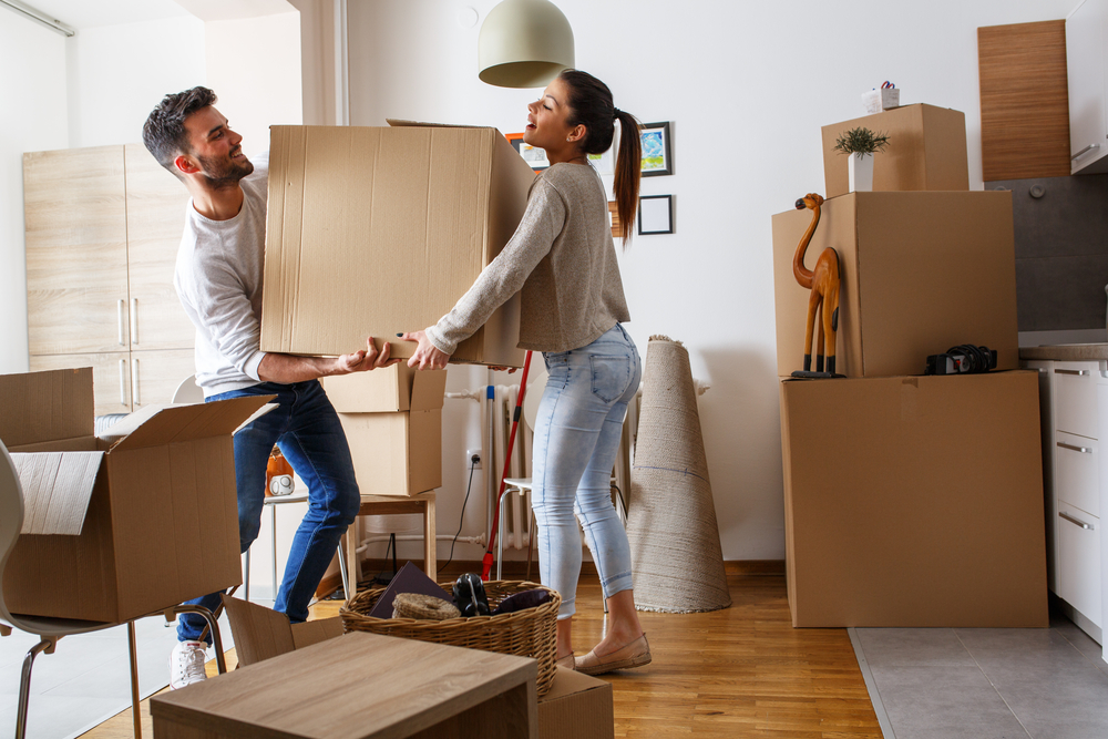 Shutterstock_568241401 Young couple carrying big cardboard box at new home.Moving house.