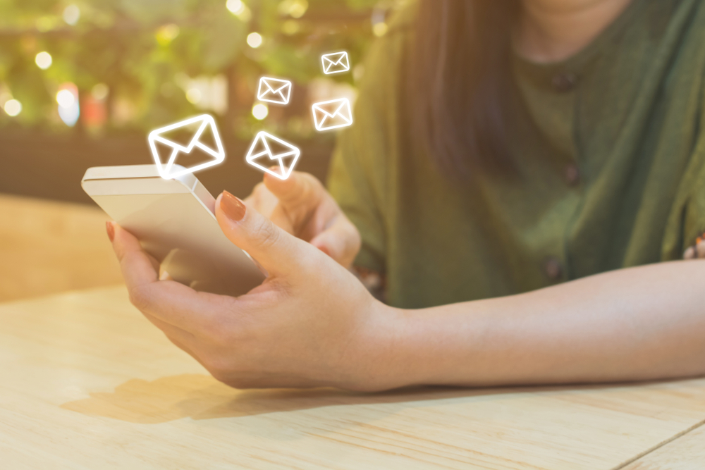 Shutterstock_793579273 Woman hand using mobile phone with e-mail application, Concept email marketing and newsletter