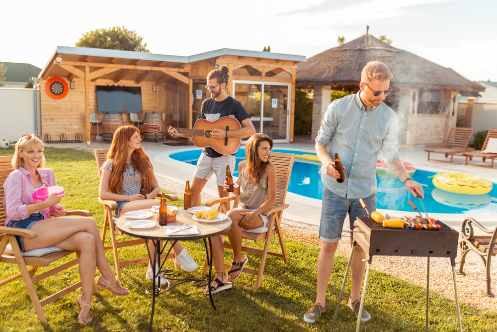 Shutterstock_1904213914 Group of cheerful young friends having fun playing the guitar and singing at backyard barbecue party, drinking beer, grilling meat and relaxing by the swimming pool