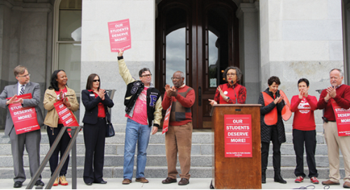 Educators hold signs on the steps of the California State Capitol in support of full and fair funding.
