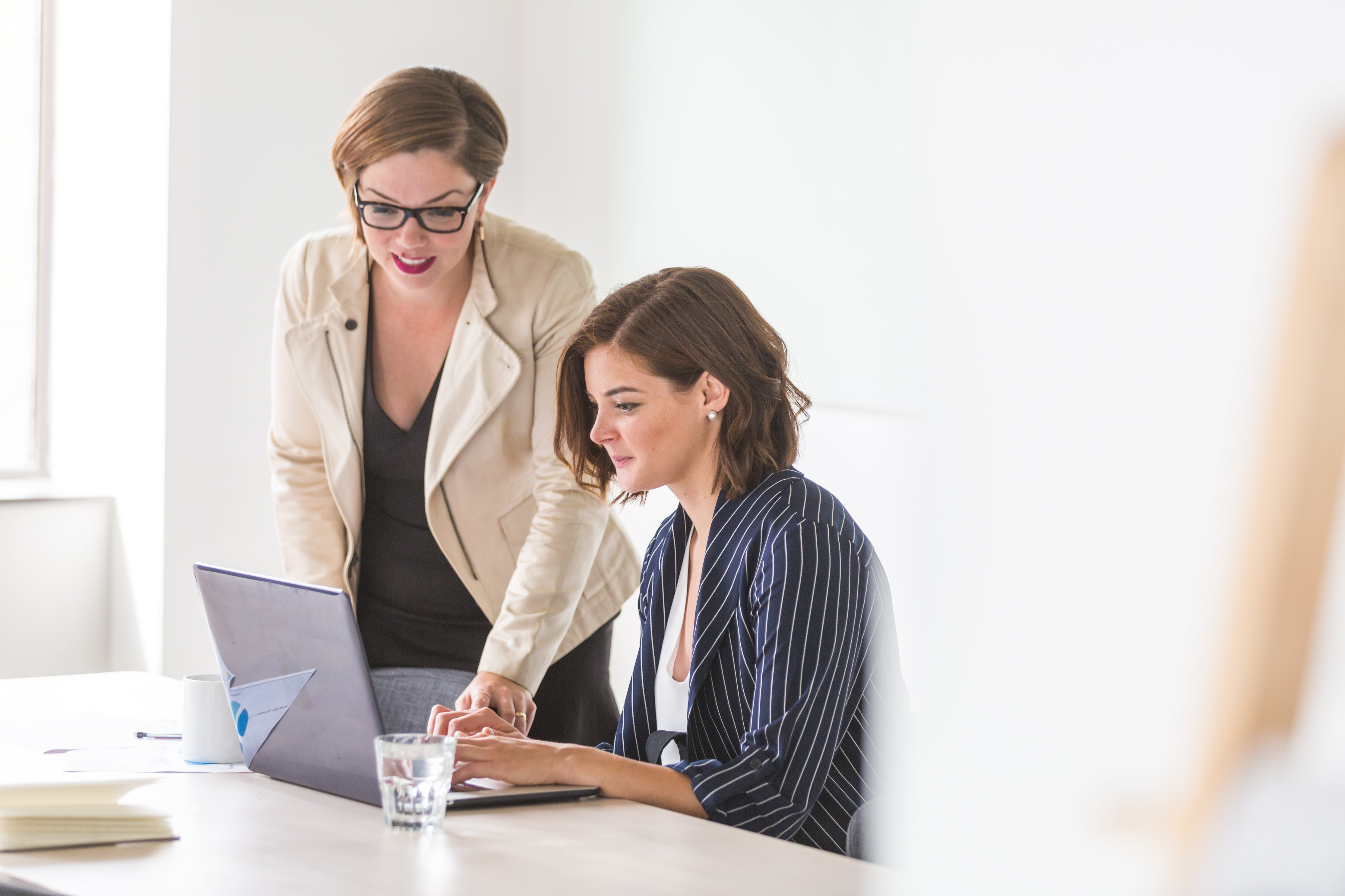 Two women collaborating over an open laptop computer