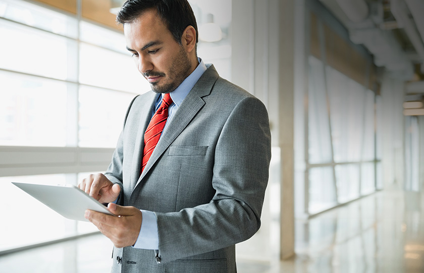 Man in a suit using a tablet