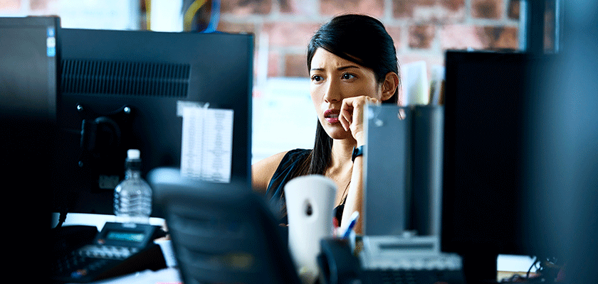 A woman looking at her computer with a concerned expression on her face